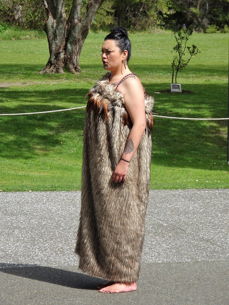 Waitangi. Maori woman in a dress  with bird feathers. She is singing.