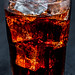 Cola with ice in glass on black background