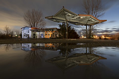 Gas Station Reflection (Notley Hawkins) Tags: clouds cloudy sky cloudysky abandoned kingdomcity callawaycounty notley notleyhawkins 10thavenue gasstation stationdegaz distributoredibenzina postodegasolina gasolinera missouri httpwwwnotleyhawkinscom missouriphotography notleyhawkinsphotography ruralphotography tree awning dusk building architecture entropy 2019 winter puddle lightpaint lightpainting warmcool bluehour thebluehour twilight february