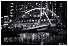 Pedestrian Bridge in Monochrome (Bob Shrader) Tags: olympuspenf olympusmzuikodigitaled12100mmf40ispro f4 110sec 1600iso raw microfourthirds mft m43 mirrorless oceania australia victoria melbourne suburb southbank precinct nature sky night water river yarrariver reflection transportation bridge pedestrianbridge yarrapedestrianbridge building skyscraper lights zoomlens olympusmzuikodigital12100mmf40ispro photoborder photoedge photoframe filmlook blackandwhite monochrome topazlabs bweffects2 cooltoneii dxo dxophotolab preset postprocessing on1 photoraw2019 aus