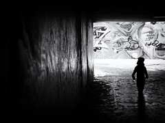 looking at the graffiti (Sandy...J) Tags: grafitti underpass urban noir olympus street streetphotography sw silhouette monochrom alone blackwhite bw light darkness city