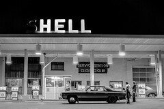 Sudbury Ontario. Approx 1973 (johnjackson808) Tags: gasoline pentaxspotmatic2 bw ilfordhp4 gas monochrome sudbury blackandwhite hell ontario streetphotography servicestation people 1970s film shell irony ironic