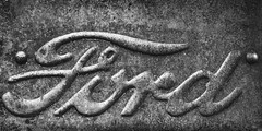 Ford emblem at Bozo's Garage, Route 66, Santa Rosa, New Mexico (Mitch Tillison Photography) Tags: ford automotive auto automobile car truck metal stamp rust bw mono emblem badge badging weathered texture nikon d5 tokina 100mm macro mitchtillison photo photography route66 santarosa bozo bokosgarage junkyard