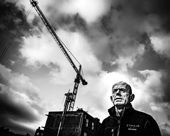 Lofty thoughts (Kieron Ellis) Tags: man crane clouds sky building thinking candid street bald contrast blackandwhite blackwhite monochrome