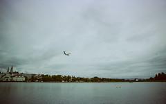 Fly Over Tjörnin (hiphopmilk) Tags: copyright©jaredyehwooehmoehfilms nikonfm2n nikonfm2 nikon fm2 35mm 135film film analog analogue kodak nikkor hiphopmilk north europe nordic iceland reykjavik reykjavík tjörnin pond lake airplane plane flight sky cloud fly