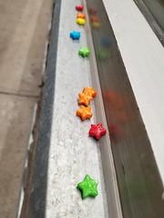 Candy stars sitting on a Giant Tiger window sill in Winnipeg. (Rob Swystun) Tags: windowsill window candy stars colour blue green orange yellow red winnipeg manitoba canada gianttiger metal concrete