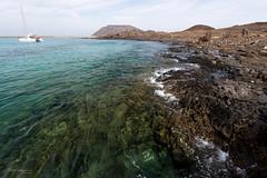 Rocky beach (piotr_szymanek) Tags: lobos fuerteventura landscape island water sea ocean yacht boat rock lava 1k 20f