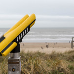 Yellow-black binoculars with inscription Galaxy in front of the beach of Zandvoort with giant chair thumbnail