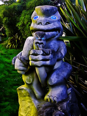 Catching Eels (Steve Taylor (Photography)) Tags: maori eel tongue holding club sculpture carving yellow blue green grey stone newzealand nz southisland canterbury christchurch grass flax bush digitalart sunrise dawn sunny sunshine bottlelakeforest bonsuter head sculpturepark southnewbrighton