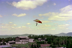 71-145 (ndpa / s. lundeen, archivist) Tags: nick dewolf nickdewolf color photographbynickdewolf 1975 1970s film 35mm 71 reel71 hanggliding hangglidingfestival franconia franconianotch newhampshire newengland mittersillalpineresort mittersill cannonmountain whitemountains worldcup competition hangglidingcompetition summer worldcupmeet meet mittersillworldcupmeet july flight inflight flying sky bluesky clouds hills mountains building lodge hotel pond fence splitrailfence pool swimmingpool crowd spectators onlookers observers trees hangglider hanggliders grass baseofthemountain tenniscourt tenniscourts people