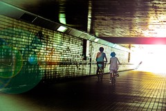 Light in the underpass (sKame-rameha) Tags: underpass light children bicycle mother people street human cycling ghost summer hallucination photoshop