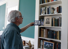 Richard Curtis looks at a photograph on the shelf at his home in Greensboro, Georgia. His mother is in the photograph, and the room that she lived in has been preserved exactly as it was when she lived in the house.