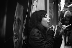 Making up. (markfly1) Tags: girl subway tube candid moment putting lip gloss make up blach hair bw mono monochromatic smiling face open mouth street photo image nikon d750 50mm prime london underground trains
