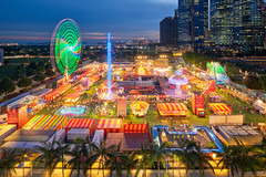 Carnival by the bay (Scintt) Tags: singapore mbs marina bay sky dramatic travel tourist attraction exploration movement motion skyline cityscape city urban modern structures architecture buildings offices shenton way cbd scintillation scintt jonchiangphotography iconic surreal epic wideangle still glow light tones dusk twilight waterfront longexposure slowshutter bluehour hotel office towers skyscrapers rafflesplace wide night evening financial business centralbusinessdistrict nikon 19mm pce tiltshift carnival fun fair celebration rides trails