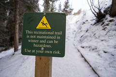 Sign warning hikers that the trail ahead is not maintained during the winter and can be hazardous (m01229) Tags: hike warn winter risk icy slippery risky advise snow bowfalls danger banffnationalpark steep liability hiking trail sport scary sign hazard closure ice