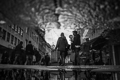 Tomorrow they'll ask again! Can I exchange it? (Black&Light Streetphotographie) Tags: mono monochrome menschen menschenbilder leute lichtundschatten lightandshadows people personen urban pfütze puddle tiefenschärfe wow water waterdrops wassertropfen rain rainy regen regentropfen raindrops regnerisch apsc sonya6000 blackandwhite bw blackwhite bokeh bokehlicious blur blurring dof depthoffield sony streetshots streets streetshooting streetportrait street schwarzweis streetphotographie sw