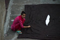 Rooftop Blanket Repair (Pedestrian Photographer) Tags: girl red sew sewing blanket repair quilt japir india eye contact