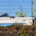 Eine der Reiterstatuen an de Hohenzollerbrücke in Köln hinter einem Zug thumbnail