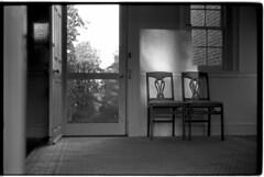 ArthurMichael10.21.18_041 (Johnny Martyr) Tags: leica leitz leicam6ttl85 leicam6ttl leicam6 leitzsummitar5cmf2 summitar leicasummitar50mm2 rangefinder 35mm bw blackandwhitefilm kodak kodaktrix kodakhc110 hc110 trix chairs twochairs sunset sunrise door lines composition math sunlight settingsun risingsun two 2 duo dos window antique scene naturallight existinglight availablelight solace solitude grace quiet peace peaceful repetition