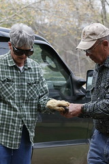 Ray Coleman hands Martha Coleman a tool in the garden.