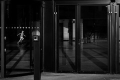 Katowice 2018 (Tomek Szczyrba) Tags: blackandwhite noiretblanc enblancoynegro inbiancoenero bw monochrome czerń biel czerńibiel noir czarnobiałe drzwi door szkło szyba glass pane dziecko dzieciak child kid street ulica streetphoto streetphotography fotografiauliczna miasto city town człowiek people ludzie polska poland bieg run light światło sunbeam cień cienie shadows