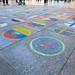 Länderflaggen auf dem Pflaster vor dem Kölner Dom dienen als Spendenaktion