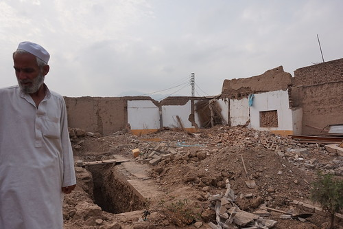 A man stands beside the remains of his home, destroyed under the collective punishment laws in Paksitan's tribal areas.