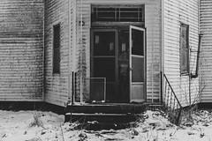 Aluminum Door (David Guidas) Tags: old church weathered winter snow dirty doors siding leica summicron blackandwhite monochrome rural worn