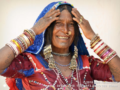 2018 Women (23a) (Matt Hahnewald) Tags: banjara lambadi gor gormati scheduledtribe matthahnewaldphotography facingtheworld people character face chintattoo facialtattoo tattoo eyes nosejewelry jewelry silver expression hairstyle traditional clothing headscarf dupatta bodylanguage gesture bothhands consent fun respect concept humanity living travel culture tradition anthropology ethnic tribal photoshoot benaulim goa india indian gypsy lamani individual oneperson female elderly woman physiognomy nikond610 nikkorafs85mmf18g 85mm 4x3ratio resized 1200x900pixels horizontal portrait halflength closeup seveneighthsview posingcamera smiling cheerful series 1of3 bangles dress ring clarity sequence colourful colour