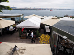 Konyali Restaurant (LeftCoastKenny) Tags: turkey istanbul topkapipalacemuseum day5 umbrellas shelters tables people deck bosphorus water city towers ships clouds