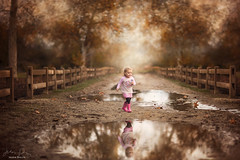 Exploring Her World ({jessica drossin}) Tags: jessicadrossin rain puddle run toddler fun happy pretty trees fence wood path road dirt reflection boots pink child kid girl wwwjessicadrossincom portrait children