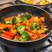 Pfanne mit gedünstetem Gemüse wie Brokkoli, Paprika und Kartoffeln auf Gasherd