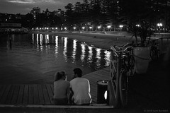 A couple enjoying early evening at Manly, on Sydney harbour, 2018  #623 (lynnb's snaps) Tags: afnikkor35mmf2d apx100 manly nikonf80 rodinal bw film night 2018 sydneyharbour agfaapx100 couple man woman romantic lights reflections beach water pier wharf people street manlywharf slr ©copyrightlynnburdekinallrightsreserved ishootfilm