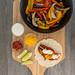Eine Fajita, Limettenschnitte, scharfe Tomatensoße, Cheddar und Limettenschmand in kleinen Glasschälchen und Paprika mit Pilzen in einer schwarzen Schale auf einem Holzbrettchen