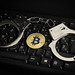 Handcuffs on computer keyboard with Bitcoin