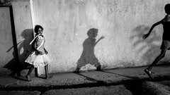 Chasing the wave of shadows (Frank Busch) Tags: frankbusch frankbuschphotography imagebyfrankbusch photobyfrankbusch asia bw blackwhite blackandwhite boy children girl hands india monochrome people running shadow street streetphotography travel travelling travelphotography villagelife wall wwwfrankbuschname
