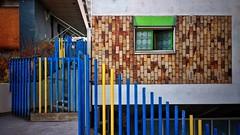 Poles (vincentag) Tags: paris france fence poles yellow blue wall bricks window
