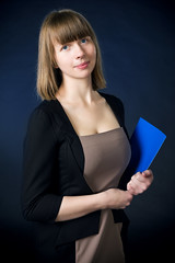 Young woman with folder in business suit (hoboton) Tags: arms background business businesswoman career caucasian corporate crossed cut elegant executive female girl hair happy management manager model office one people person portrait professional smart standing studio success successful suit well woman worker young dress folder file selfbinder dark blue black