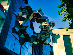 UFO - Unidentified Floating Object (Steve Taylor (Photography)) Tags: ufo alien fins digitalart sculpture architecture window blue green cream yellow metal glass newzealand nz southisland canterbury christchurch city tree branch leaves shape