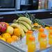 Frisch gepresster Fruchtsaft in Flaschen auf Eis, daneben Bananen, Äpfel, Ananas und Orangen