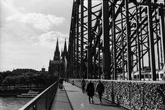 Walking in Cologne (Christophe_A) Tags: cologne germany europe christophe christopheanagno christopheanagnostopoulos wwwchristopheanagnocom global ambassador tokina tokinaopera opera 50mm nikonf5 nikon ilford pan400 ilfordpan400 self develop filmonly film135 film black blackwhite blackandwhite white street photography travel analog monochrome bridge people sky city rhine river explored explore flickr