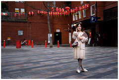 alone in chinatown (Silver Machine) Tags: london chinatown chineselanterns streetphotography street candid girl standing mobilephone fujifilm fujifilmxt10 fujinonxf35mmf2rwr