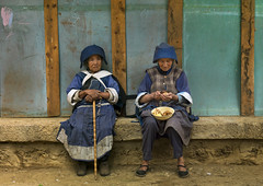Naxi Minority Women Sit On A Bench, Lijiang, Yunnan Province, China (Eric Lafforgue) Tags: a0007847 adultsonly asia china colorpicture costume day frontview fulllenght horizontal lijiang lookingatcamera naxi oldtown outdoors realpeople street tranquility twopeople twopersons unescoworldheritagesite yunnan yunnanprovince