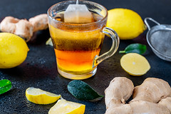 Ginger root tea with lemon on dark background