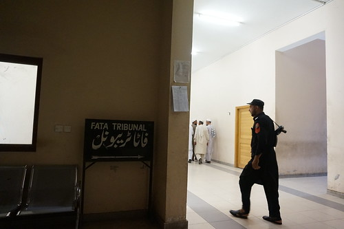 Tribesmen confer, as guard walks past entrance to a court in Peshawar setup to hear appeals from Pakistan's tribal areas.