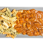 Served cooked colorful macaroni on the plate with meat goulash thumbnail