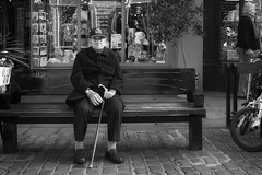 One is the loneliest number. Part 2 (markfly1) Tags: elderly man sitting alone lonely solitary solitude frail walking stick bench cap hands christmas time family sharing solo candid image street photo nikon d750 35mm manual focus lens nikkor black white mono bw baw chichester uk england city town urban scene shop fronts windows decorations