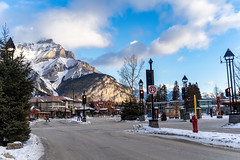 Banff, Alberta Canada - Jan 21, 2019: View of downtown Banff National Park, a Unesco World Heritage Site, during the winter. Cascade Mountain in background (m01229) Tags: intersection historic street western city tourist destination traffic streetview banffnationalpark national townsite outside banff site architecture canada facade souvenirs building winter shopping canadian rocky rockymountains popular mountains vacation scenic town rockies tourists shop editorial unesco sidewalk avenue travel outdoors alberta banffavenue heritage park touristattraction tourism store mountain