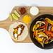 Eine Fajita, Limettenschnitte, scharfe Tomatensoße, Cheddar und Limettenschmand in kleinen Glasschälchen und Paprika mit Pilzen in einer schwarzen Schale auf einem Holzbrettchen auf weißem Hintergrund von oben fotografiert
