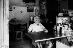 Old School (D. R. Hill Photography) Tags: bangkok thailand thai asia southeastasia city urban restaurant street streetphotography environmentalportrait portrait man monochrome blackandwhite grain film analog analogue 135 35mmfilm contax contaxg1 g1 carlzeissplanar35mmf2 zeiss planar 35mm ilford ilfordfp4plus125 fp4 ilfordfp4